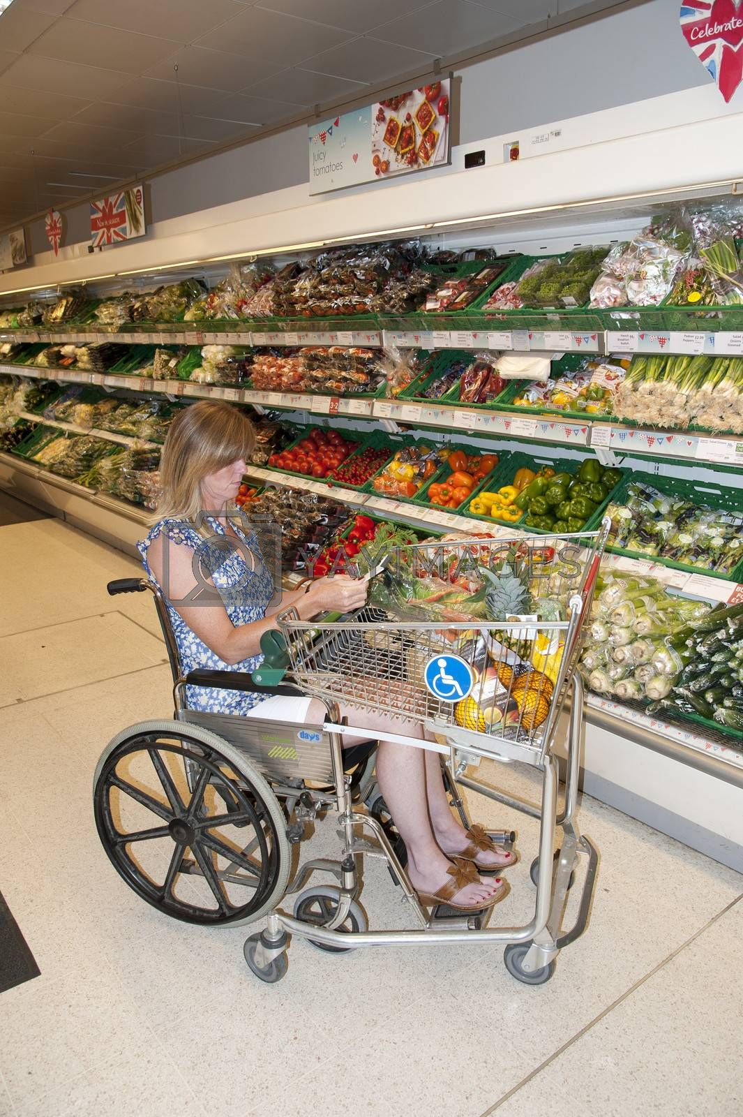Woman in a wheelchair shopping for vegetables in a supermarket