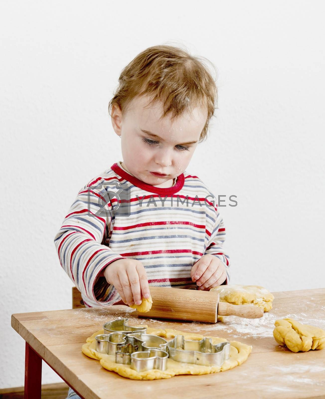 vertical image of 2 year old child making biscuit  at wooden desk