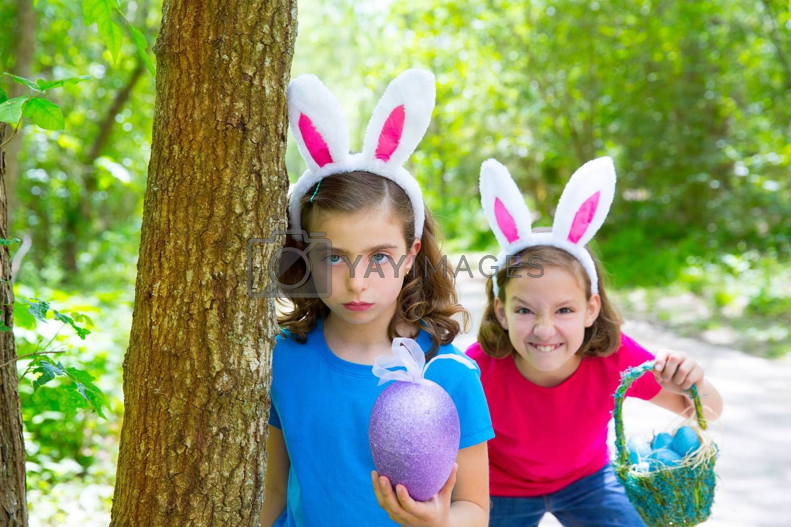 Easter girls playing on forest with bunny teeth expression outdoor