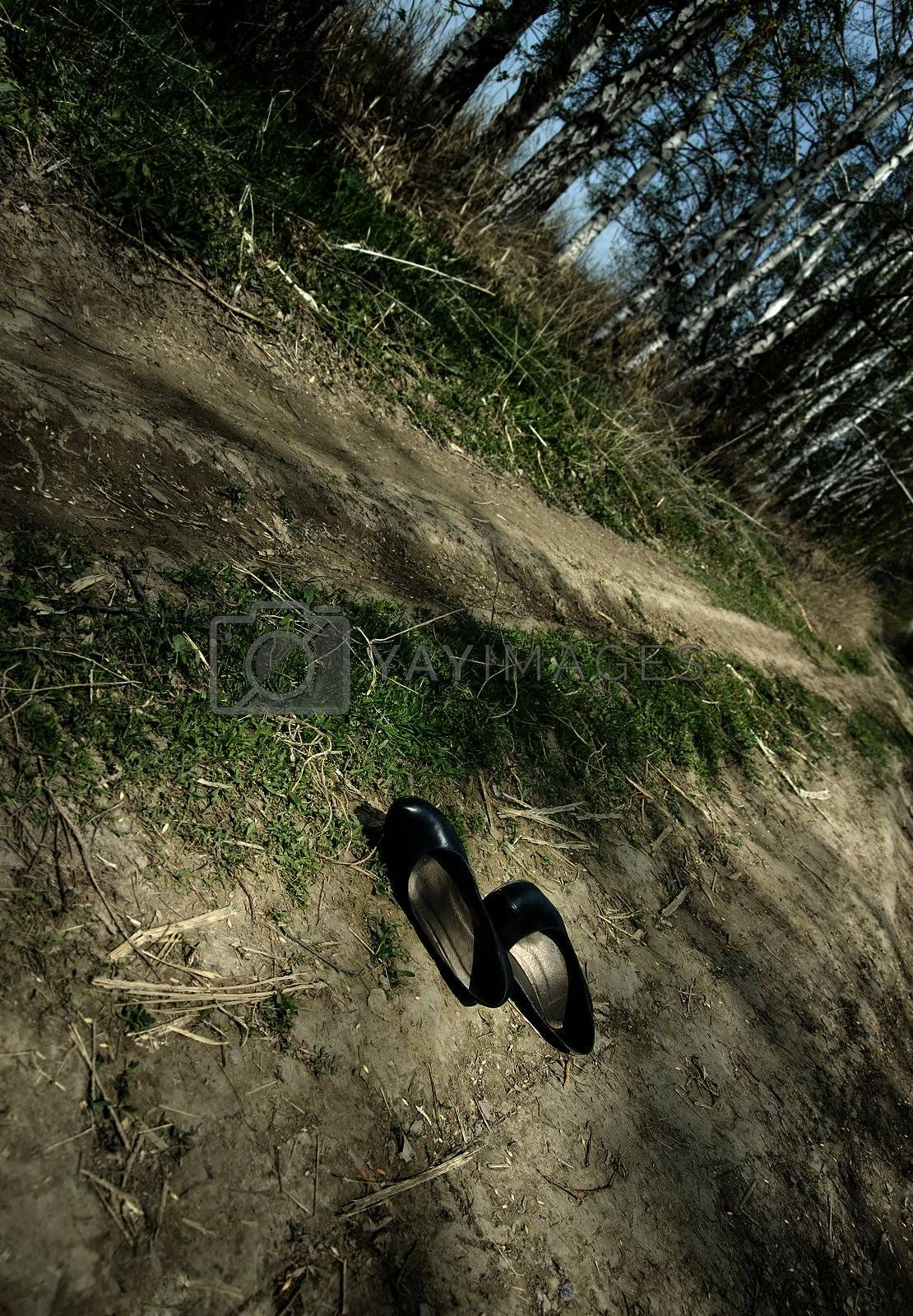 Photo of the lost old shoes on the forest pathway