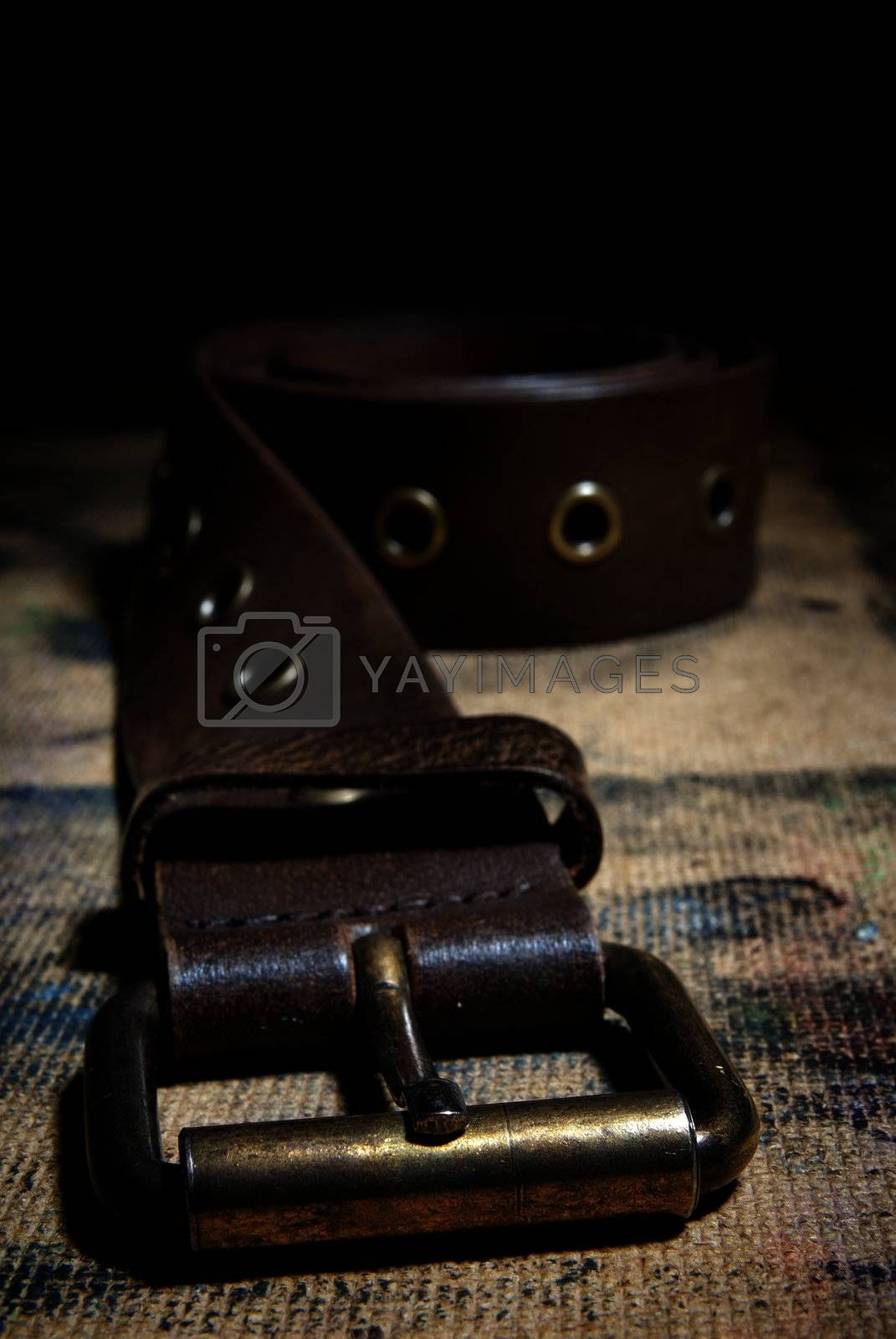 Close-up photo of the leather belt on the dirty surface