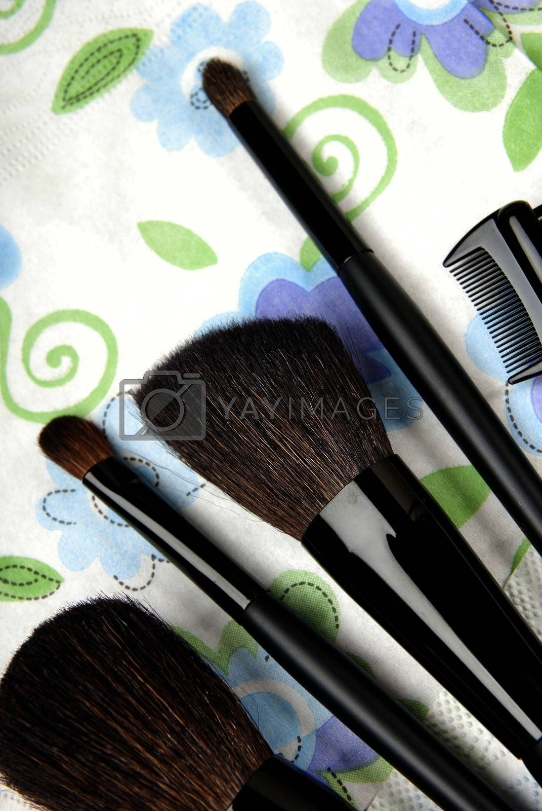 Close-up photo of five make-up brushes on a colorful background