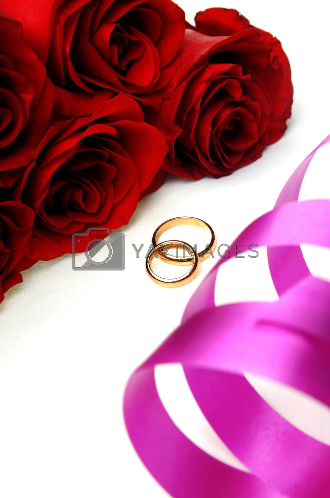 Bunch of flowers and wedding rings with ribbon