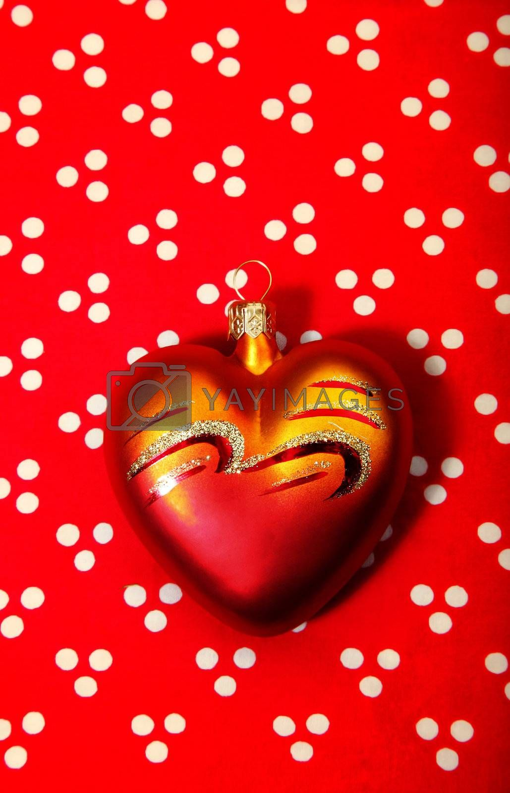 Toylike heart on a red background as a symbol of Valentine's Day or Christmas