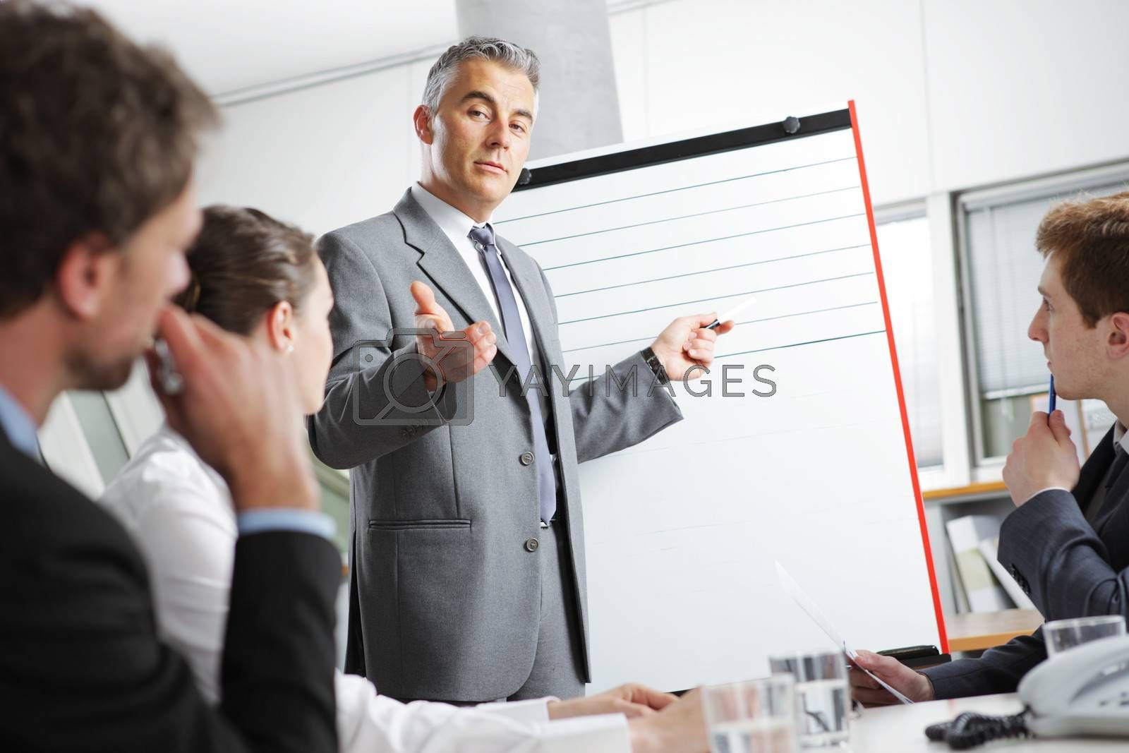 Mature businessman giving a presentation to his colleagues