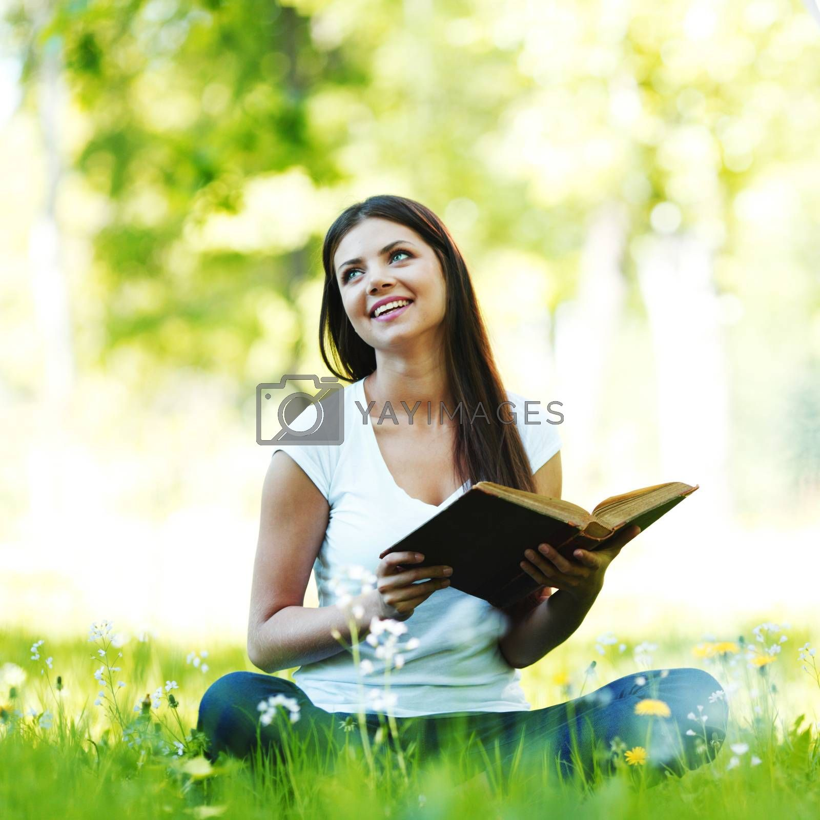 Woman reading book in park outdoors