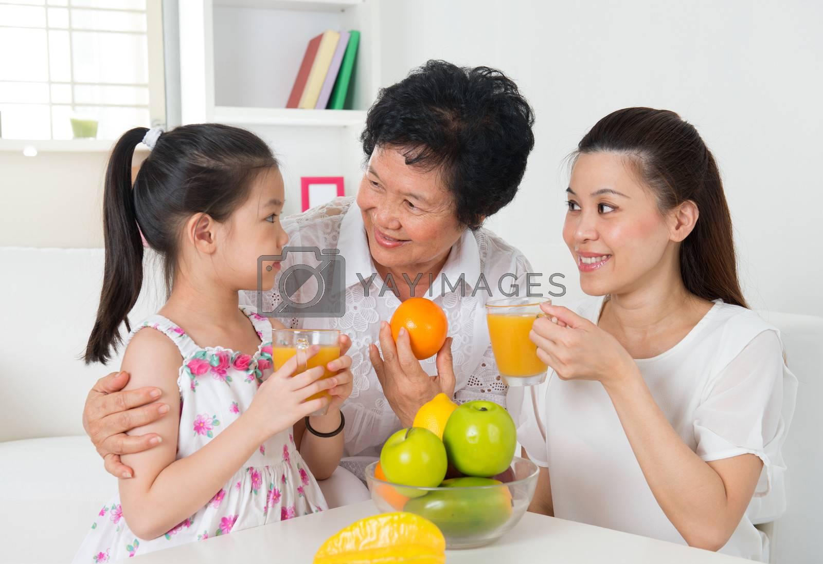 Asian family drinking orange juice.  by szefei