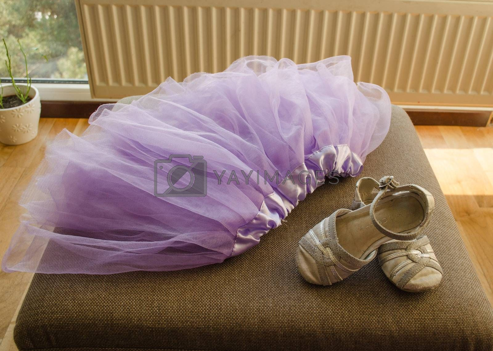 gorgeous bright lilac girls skirt with a silk ribbon around the waist and a small gray sandals