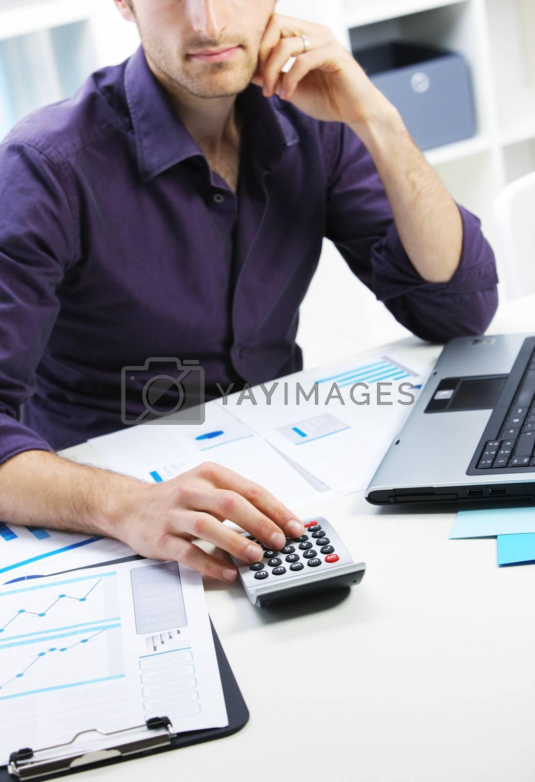 Business man checking financial data on calculator.