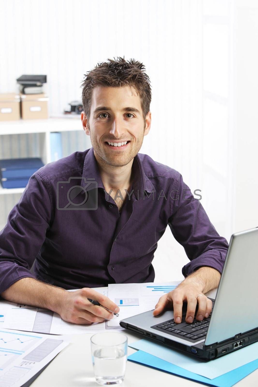 Young businessman working on laptop, looking at camera, smiling