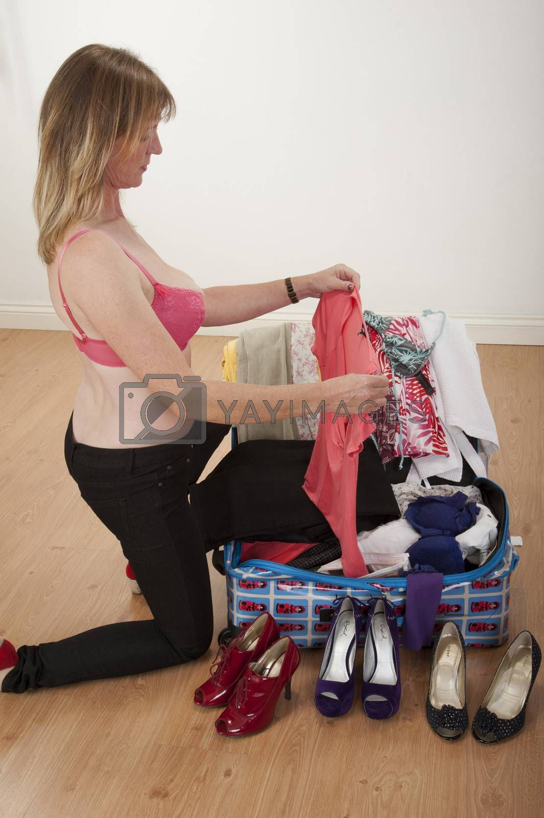 Royalty free image of Woman packing suitcase for holidays by peter_t