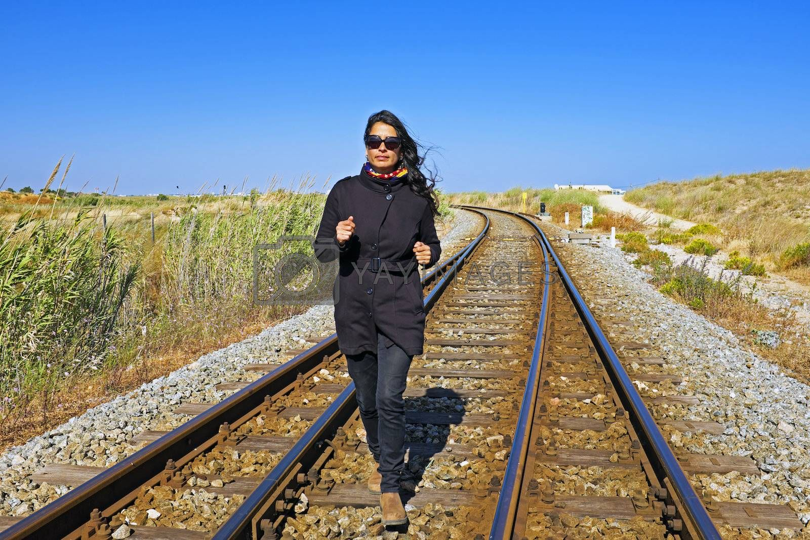Royalty free image of Young beautiful woman running on a railroad track by devy