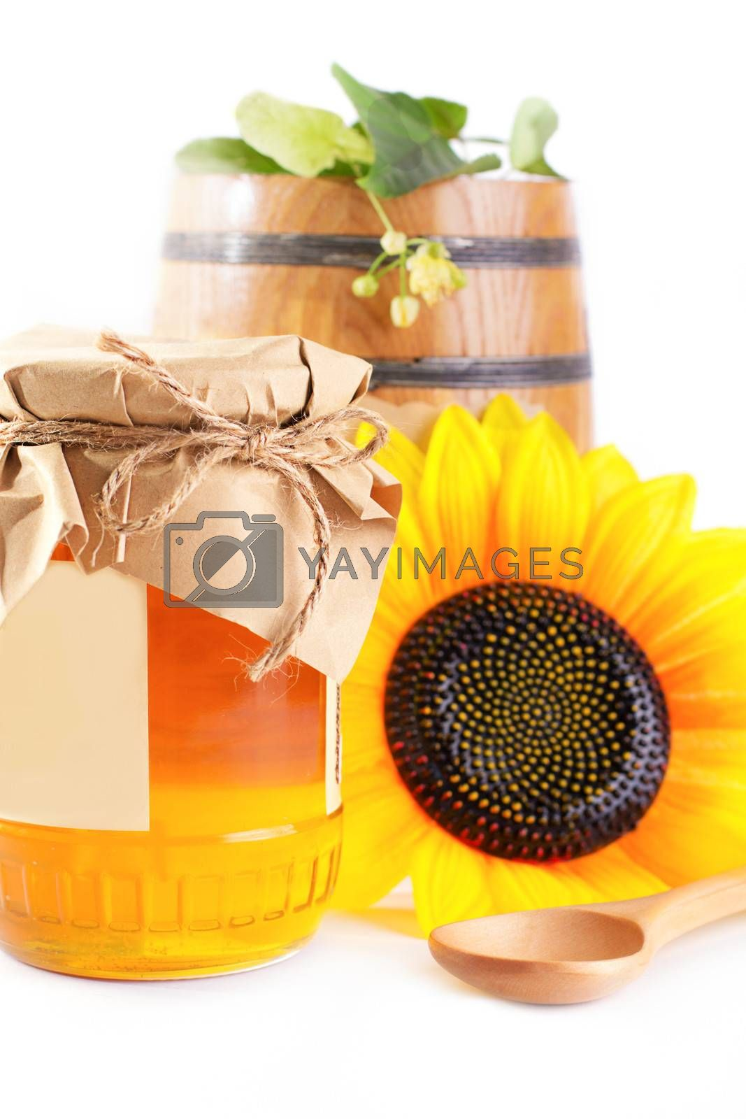 Royalty free image of Jar and barrel with honey and flowers by Angel_a