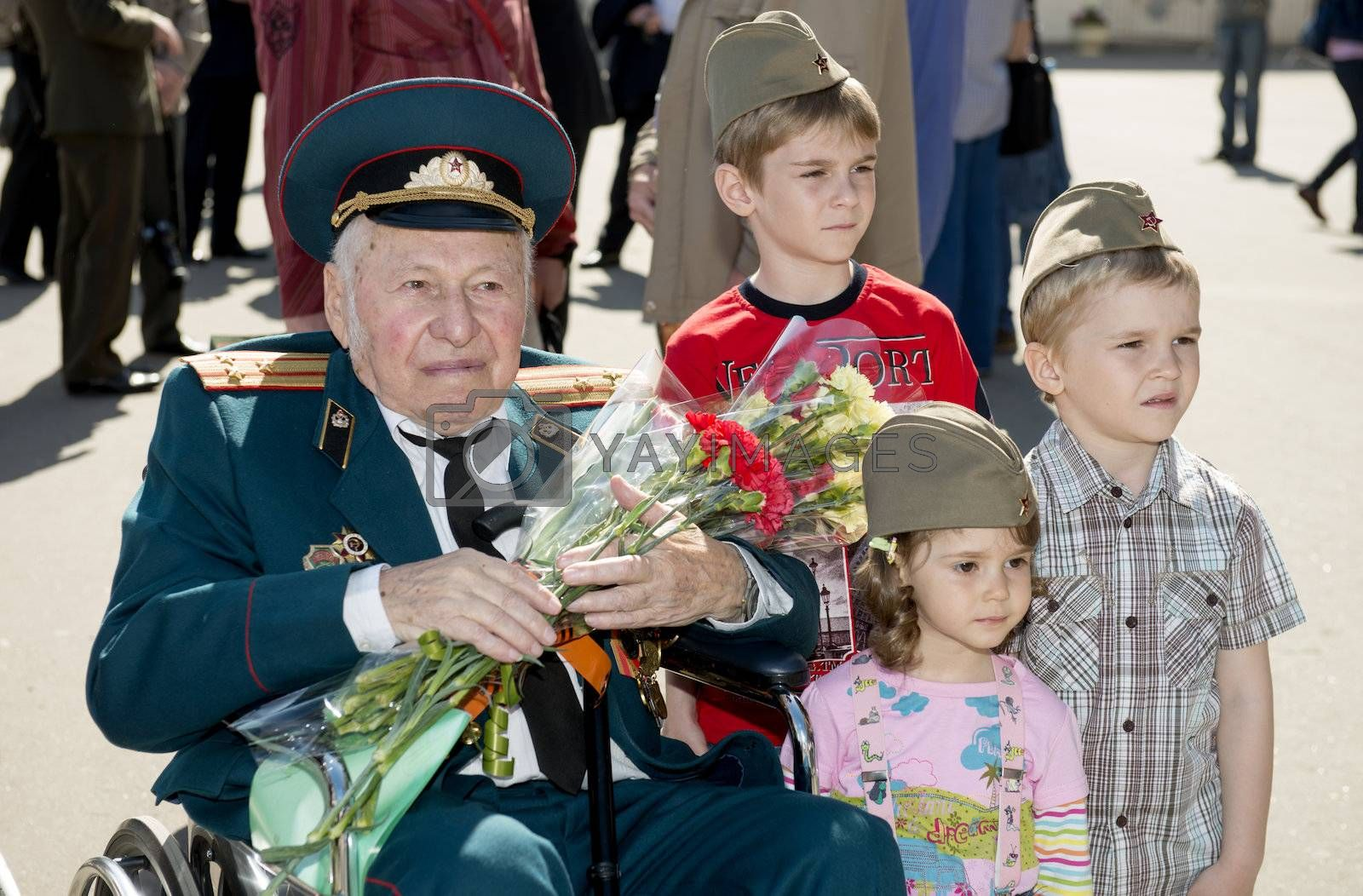 Moscow, Russia - May 9, 2013: Old man veteran of WWII in uniform decorated with numerous orders and medals bearing bunch of flowers and three children during festivities devoted to 68th anniversary of Victory Day.