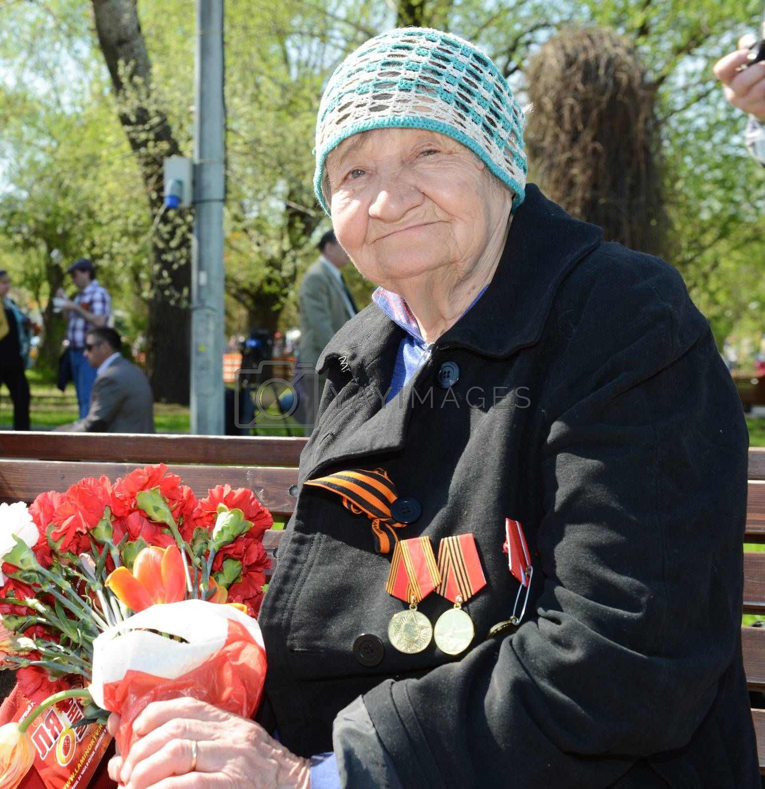Moscow, Russia - May 9, 2013: Old woman veteran of WWII  bearing bunch of flowers during festivities devoted to 68th anniversary of Victory Day.