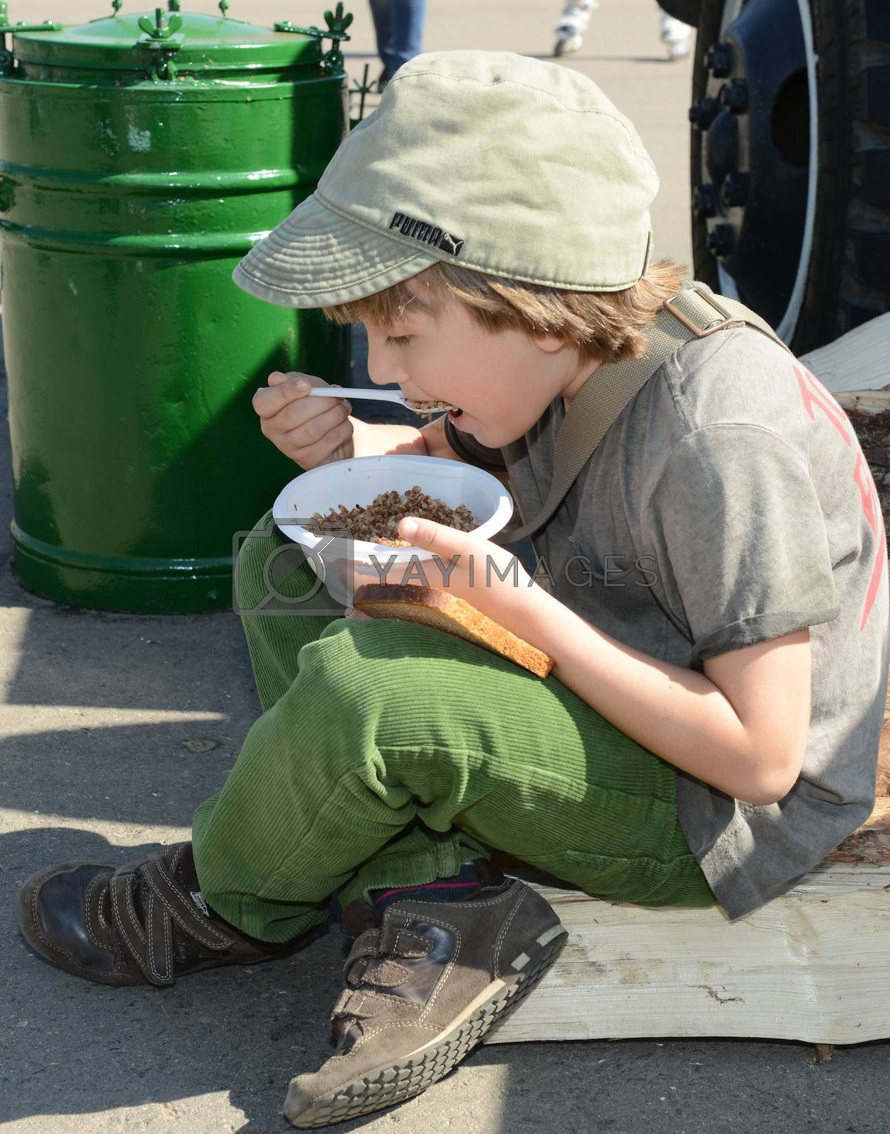 Moscow, Russia - May 9, 2013: Boy eating porridge soldier in the military field kitchen during festivities devoted to 68th anniversary of Victory Day
