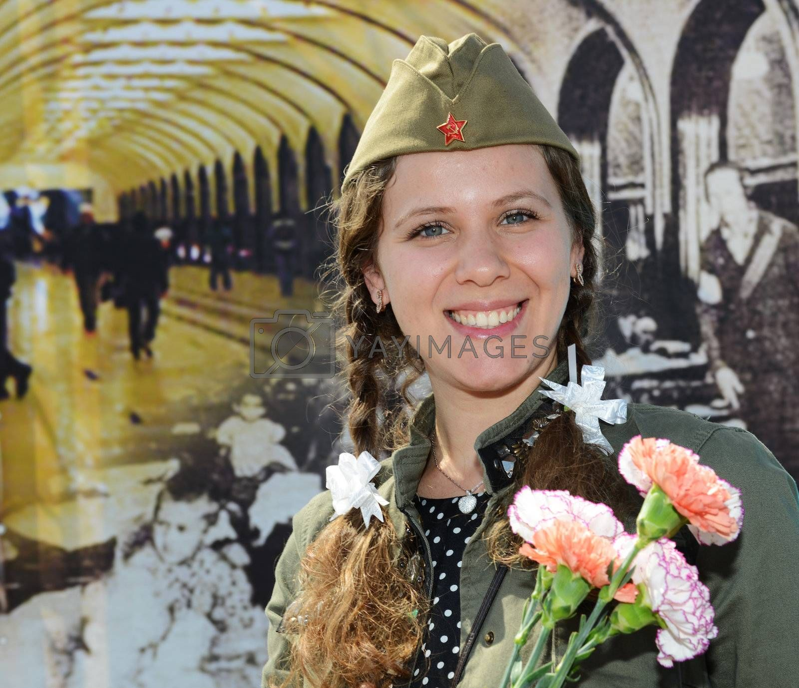 Moscow, Russia - May 9, 2013: Portrait of young girl in uniform decorated bearing bunch of flowers during festivities devoted to 68th anniversary of Victory Day