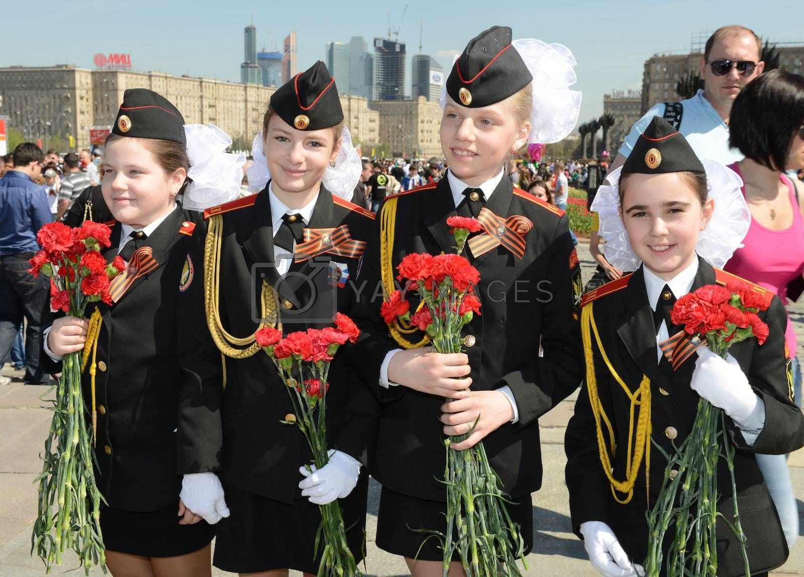 Moscow, Russia - May 9, 2013: Four young girls in uniform decorated with bearing bunch of flowers during festivities devoted to 68th anniversary of Victory Day.