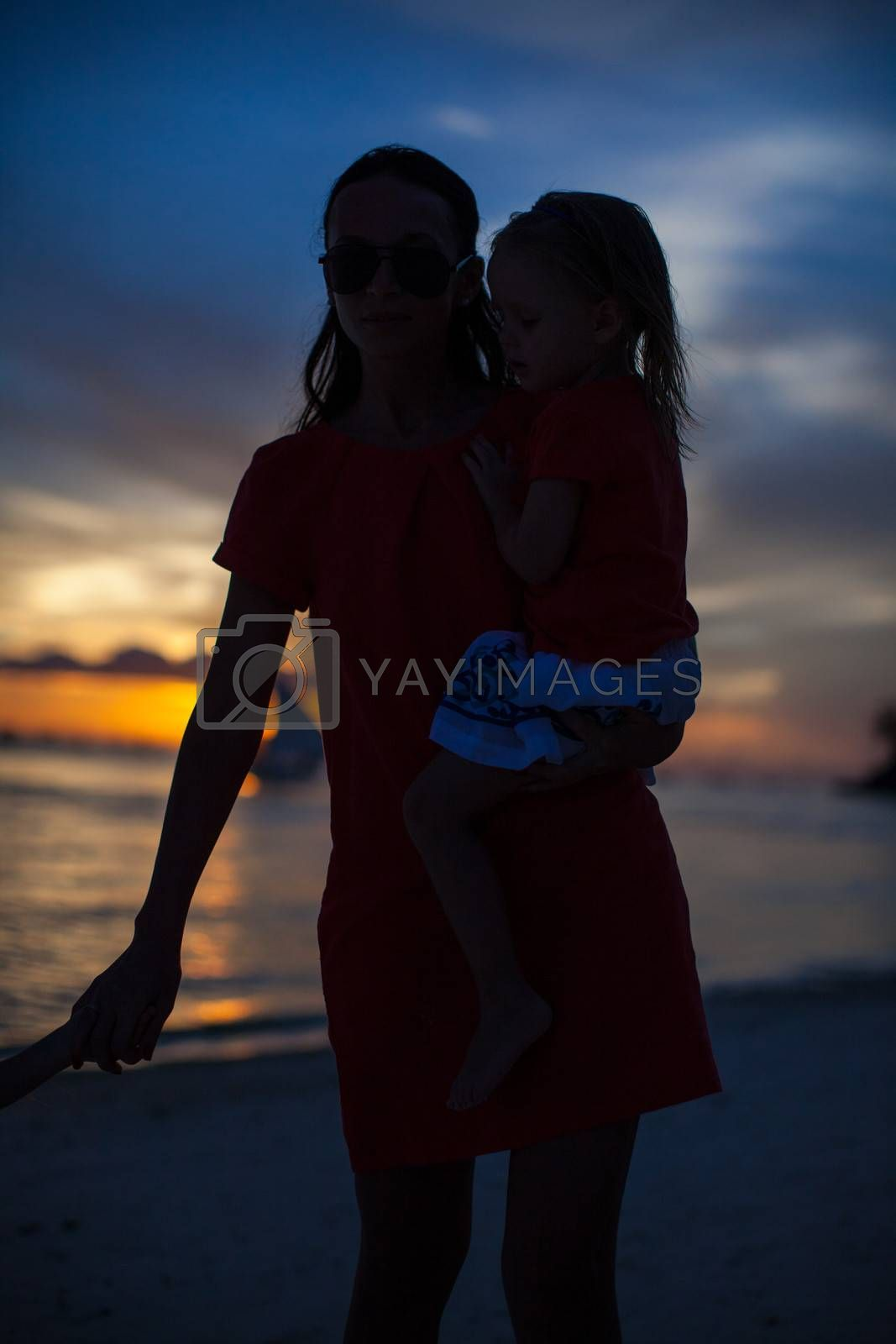 Mom and daughter silhouette in the sunset at the beach on Boracay