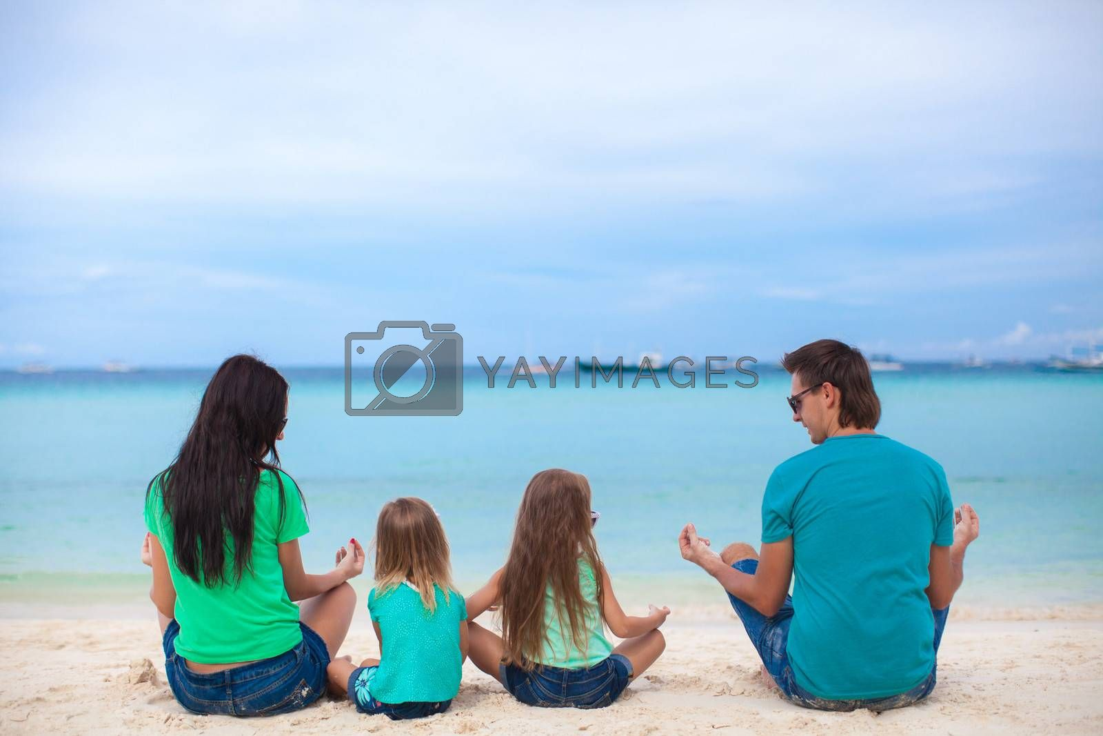 Rear view of a family of four sitting in the lotus position on the beach