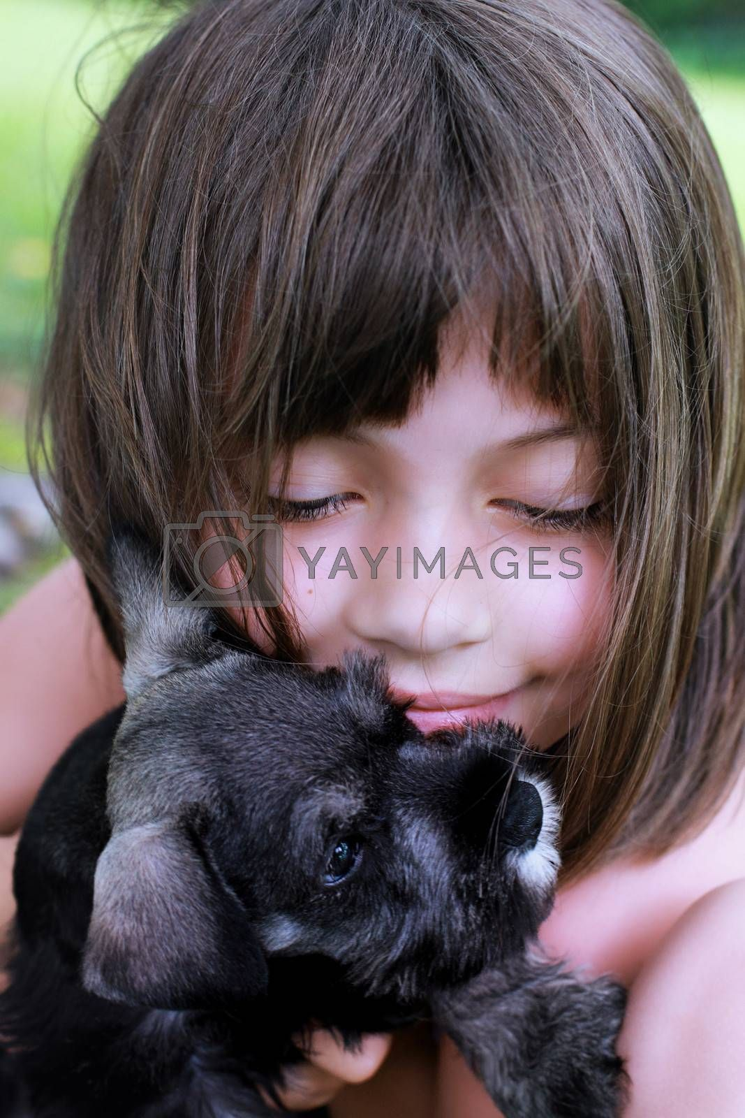 Little girl hugging her Mini Schnauzer puppy. Extreme shallow depth of field with selective focus on child's face.