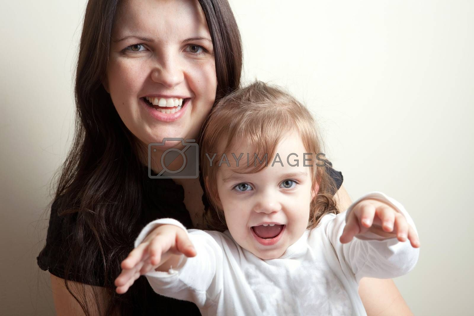 Toddler age girl sitting with her smiling mother.