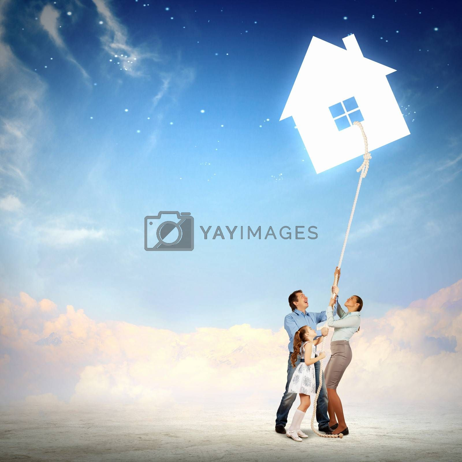 young family pulling rope with an image of house. Collage