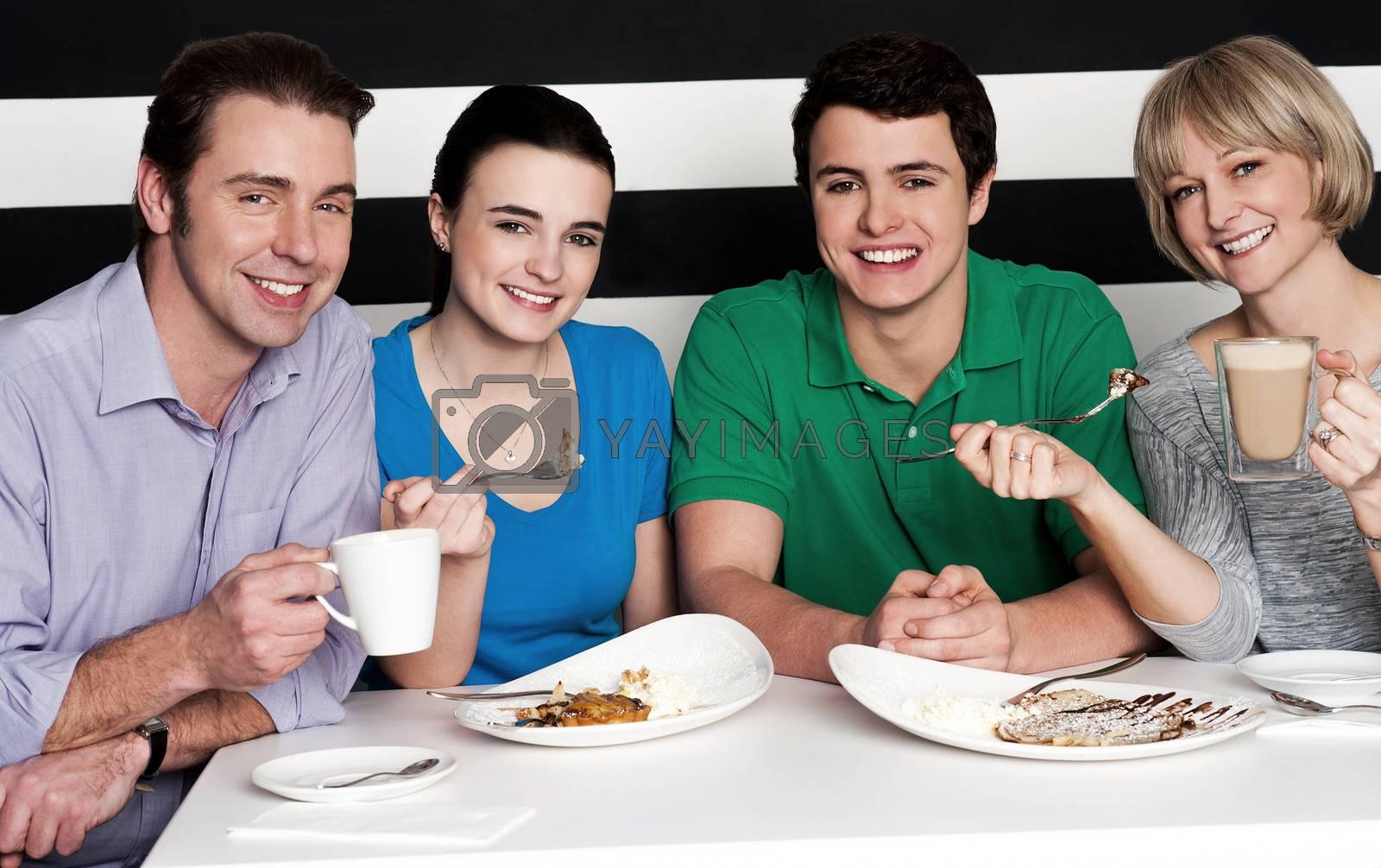 Cheerful family of four relishing nice cuisine breakfast and chocolate shake
