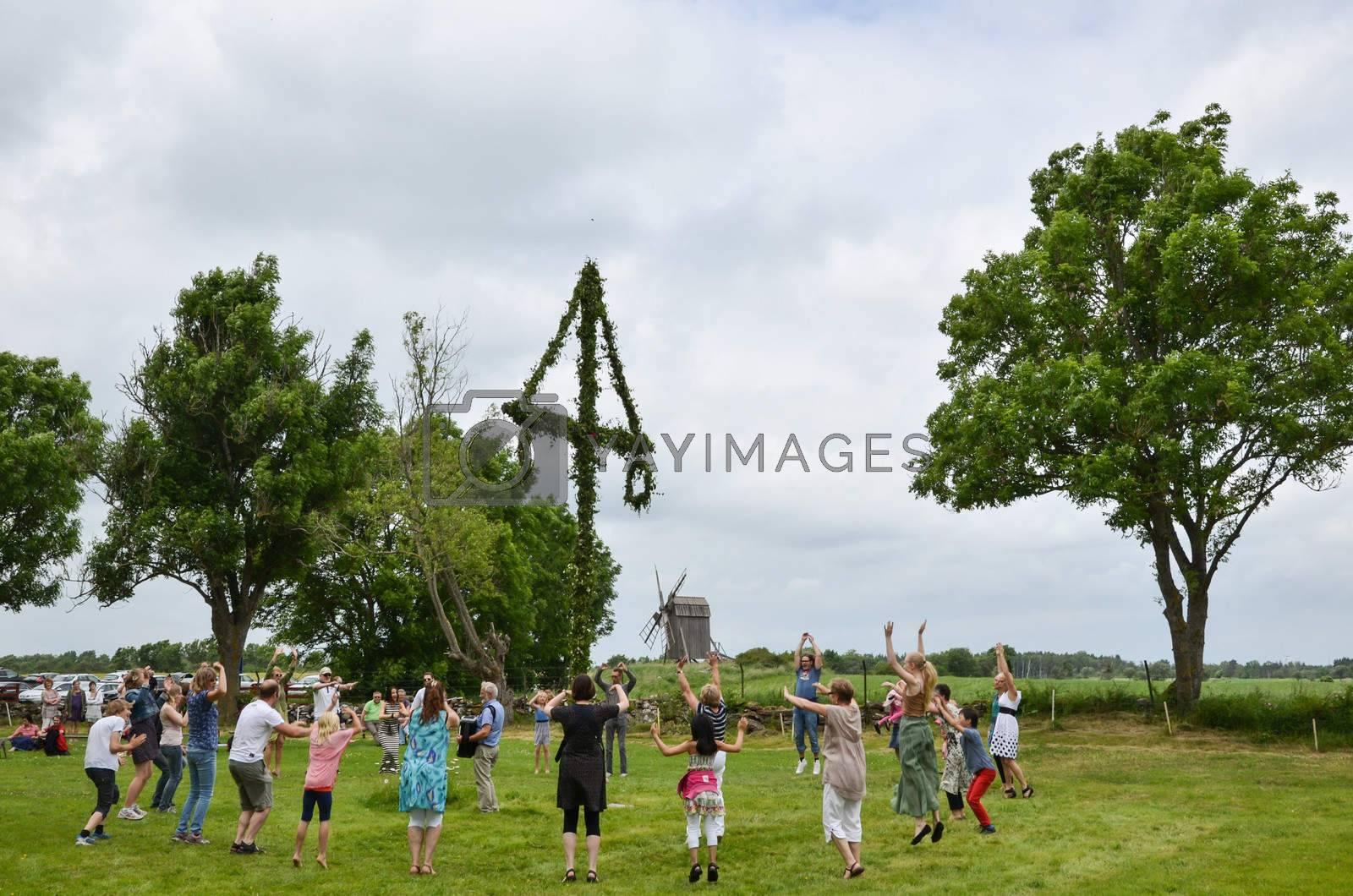 Oland, Sweden on June 22, 2013 - People celebrating midsummer dancing around a midsummer pole in Sweden