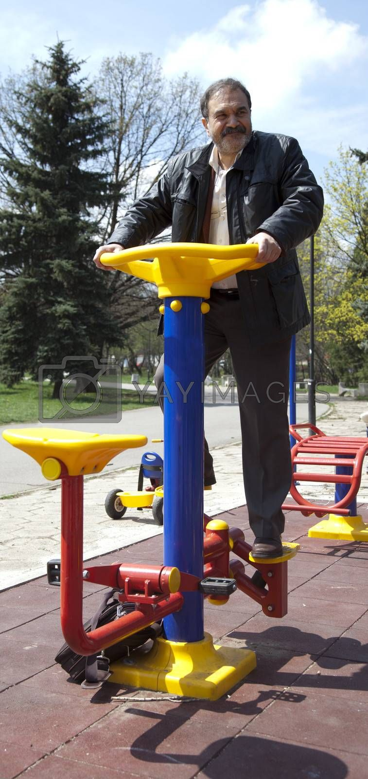 Adult man exercising on colourful fitness machine in park