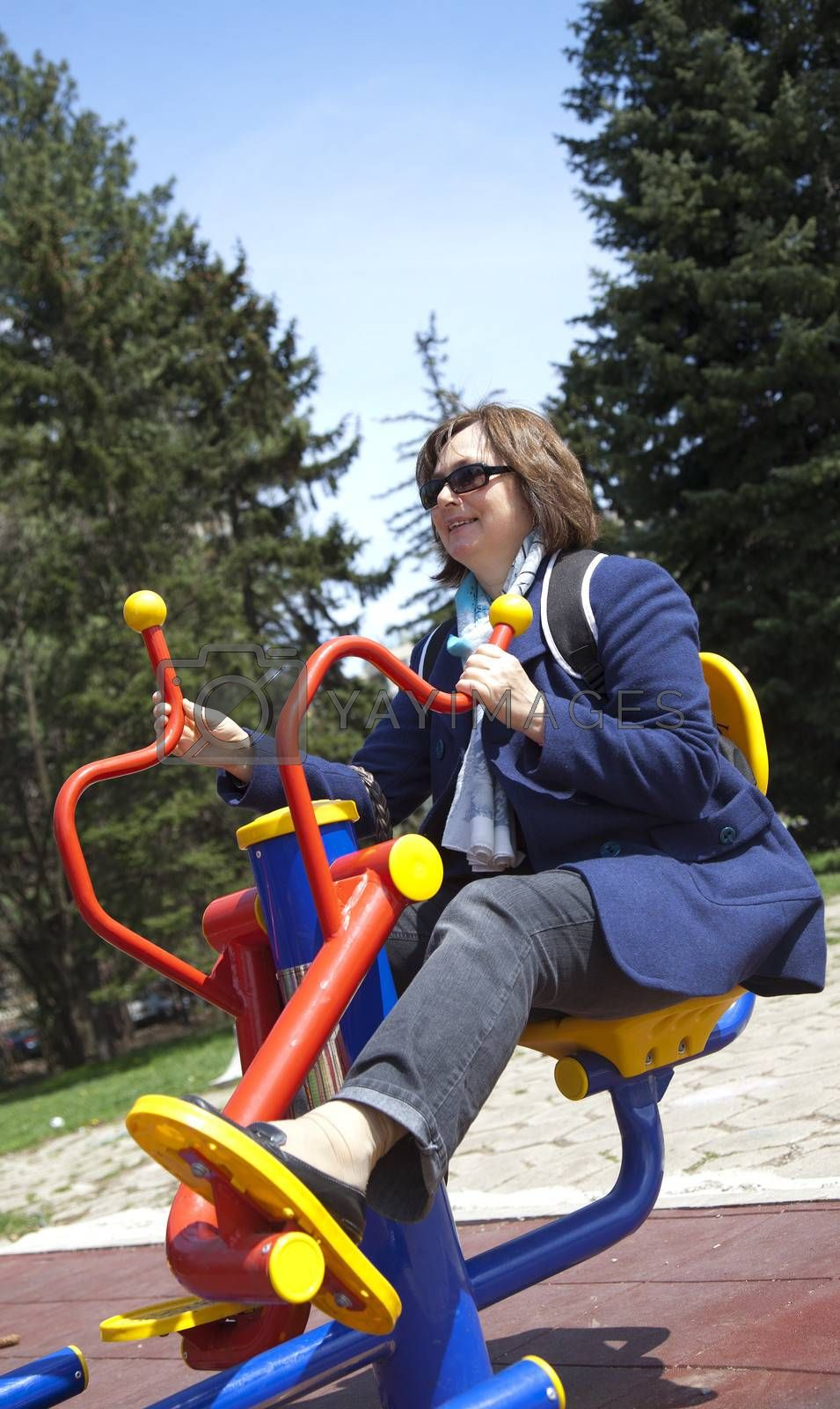 Adult woman with sunglasses exercising on stepper fitness machine in park