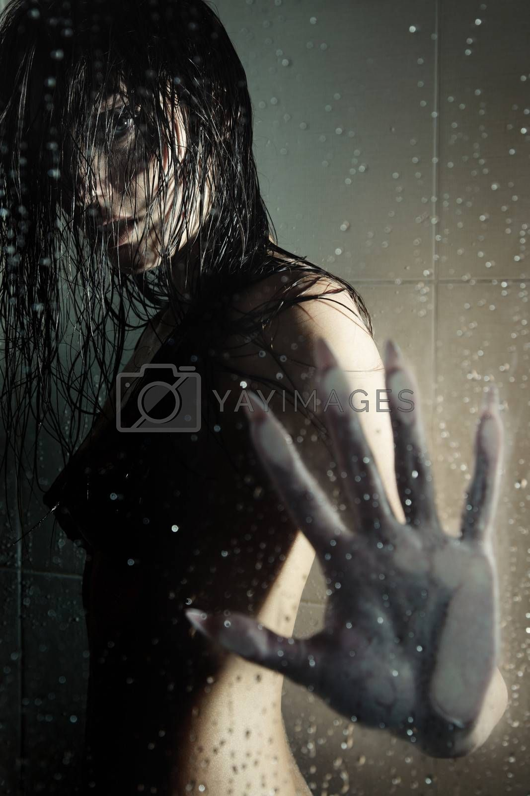 Female witch standing in the shower room behind the wet glass. Artistic darkness and texture added