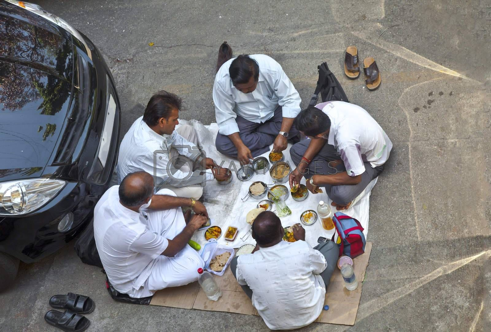 Ariel shot of Indian private car drivers having lunch in a public car park near their vehicles. Location of shot, Bombay India