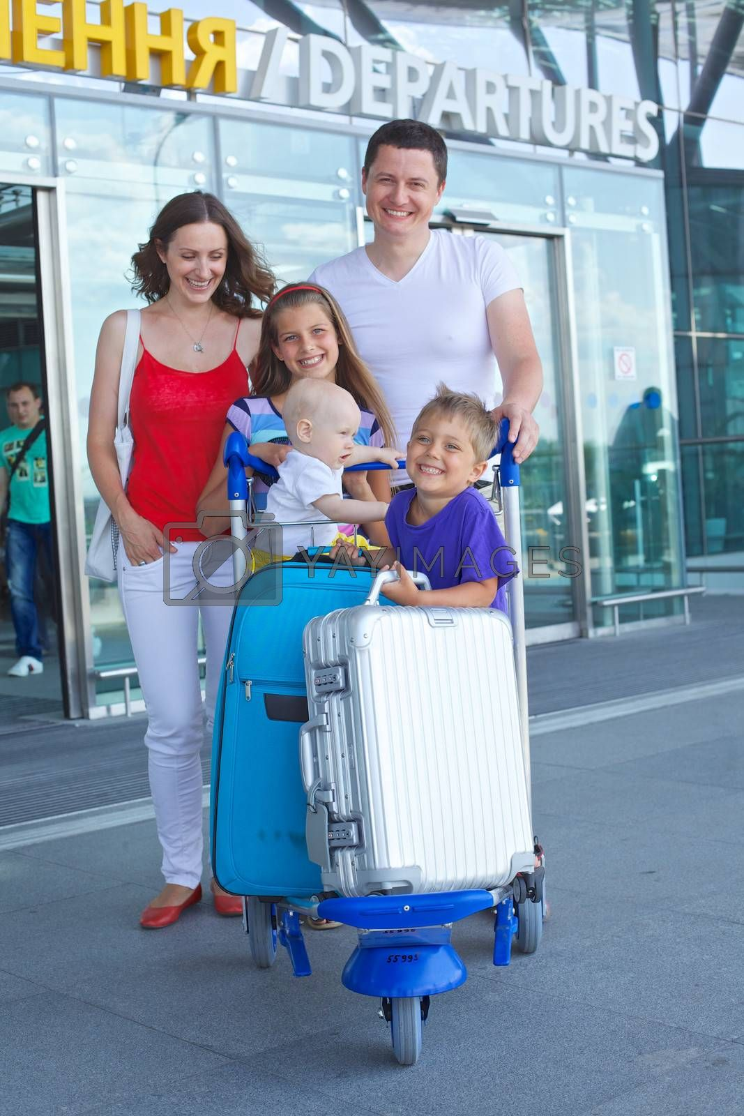 Standing traveling family of five with suitcases in airport