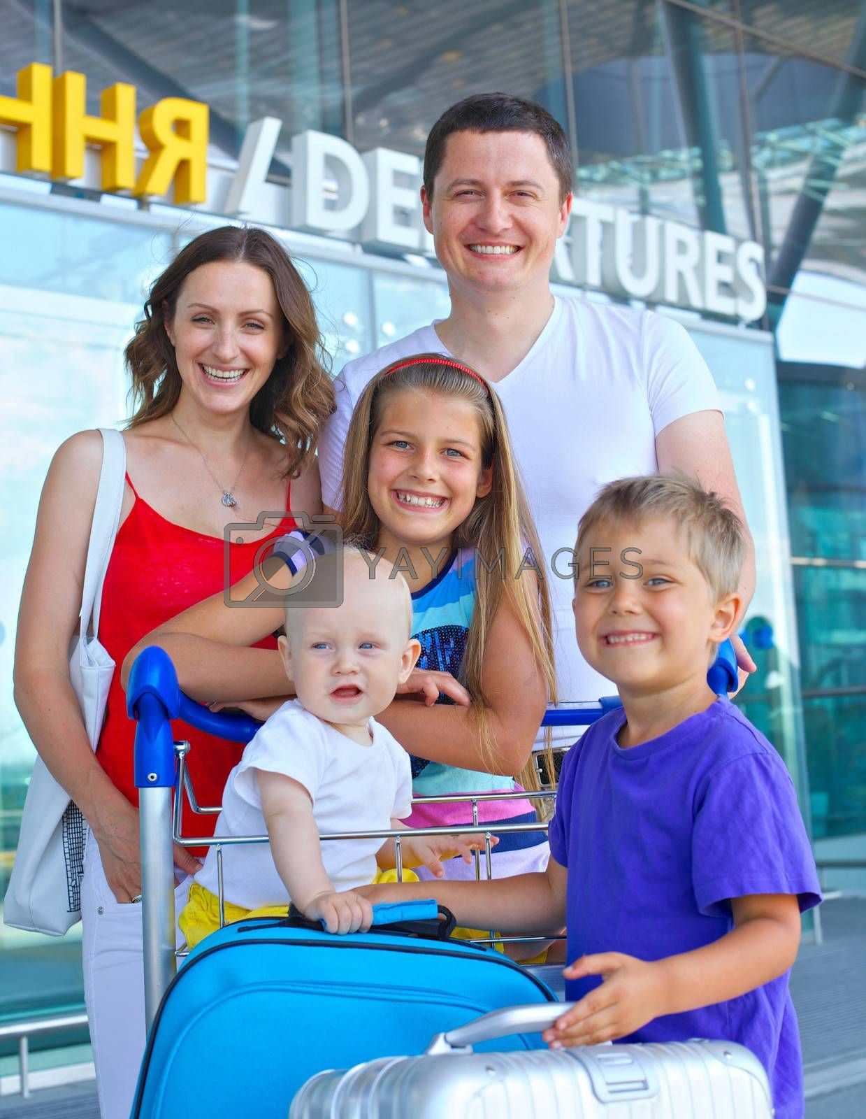 Portrait of traveling family of five with suitcases in airport