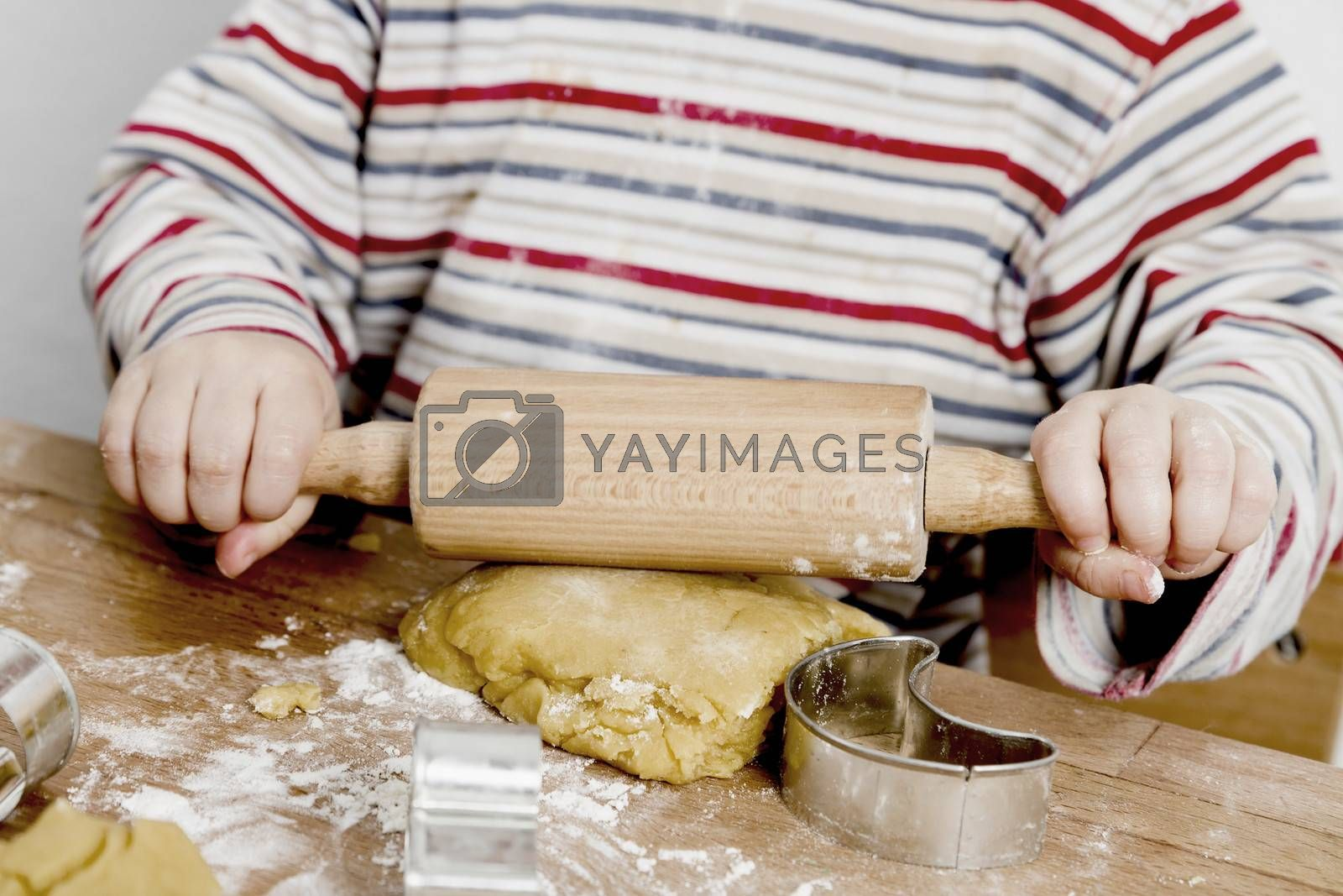 image of hands and desk. child is making cookies with a rolling pin