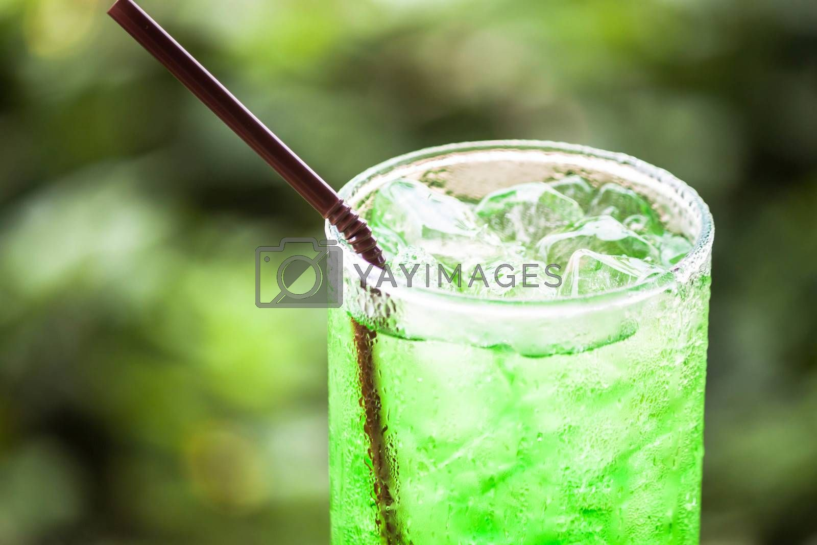Glass of iced green drink with straw