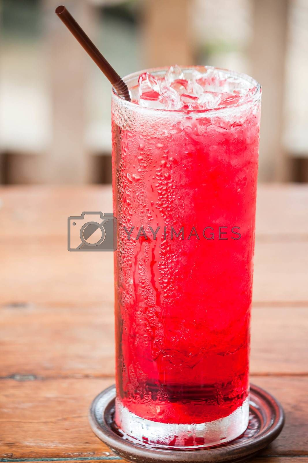 Glass of cold red drink with straw