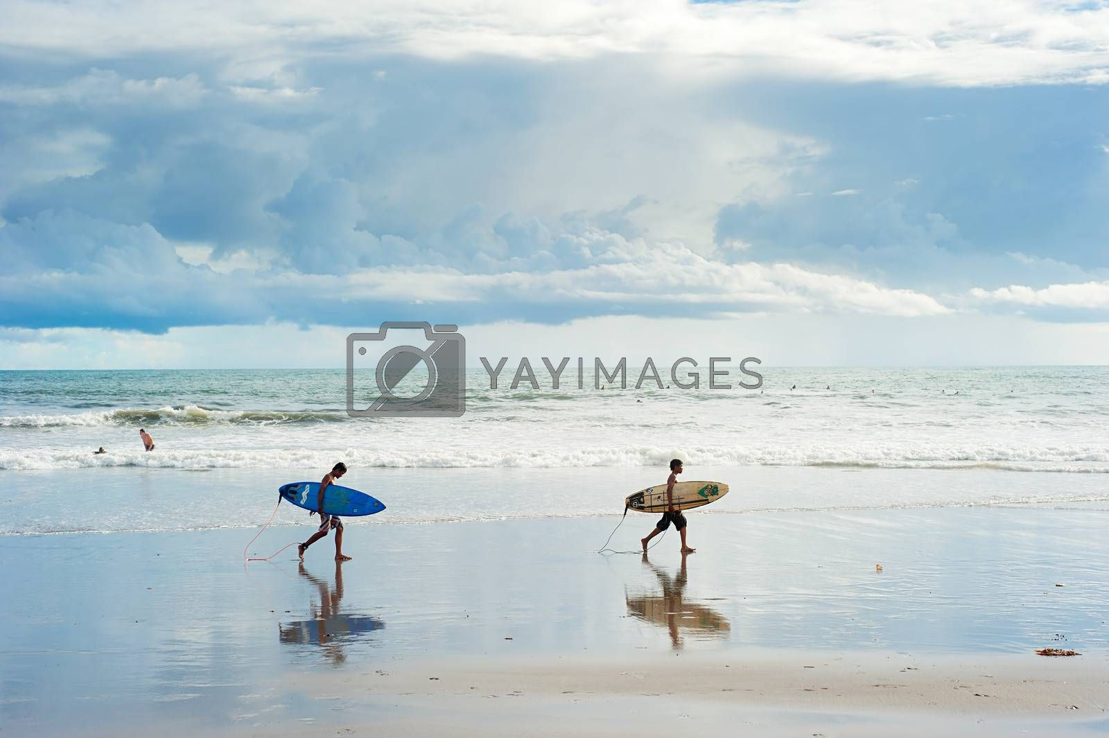 Bali island; Indonesia - March 16, 2013: Local boys walking with a surfboards on the beach. Bali is one of the top of world surfing destinations.