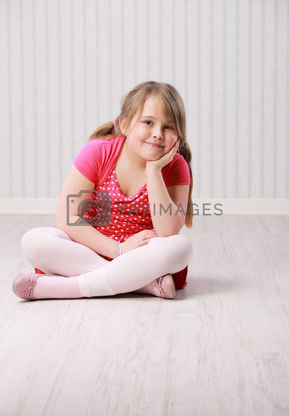 Portrait of a little beautiful girl sitting on floor