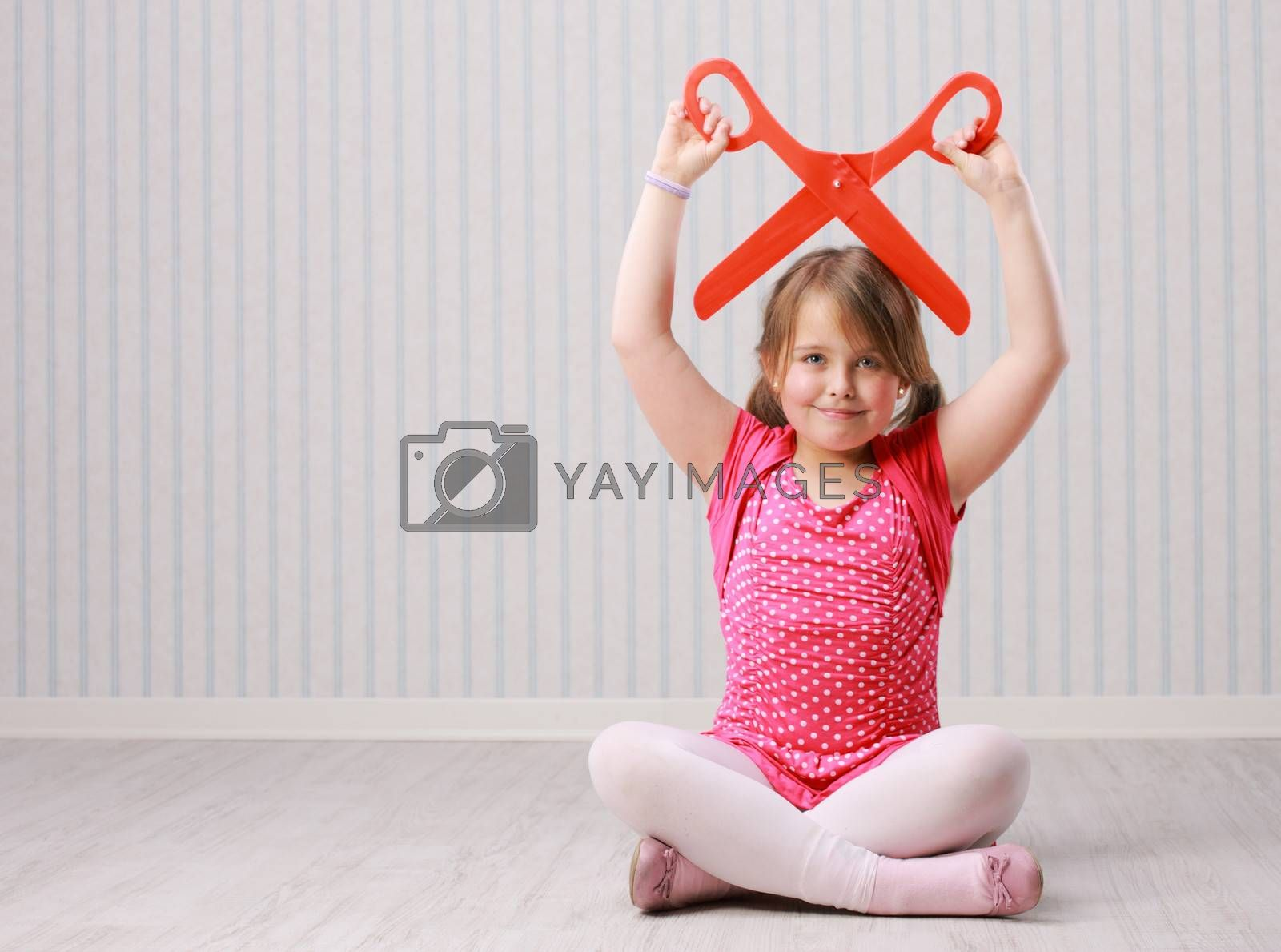 Portrait of a little beautiful girl with a giant scissors