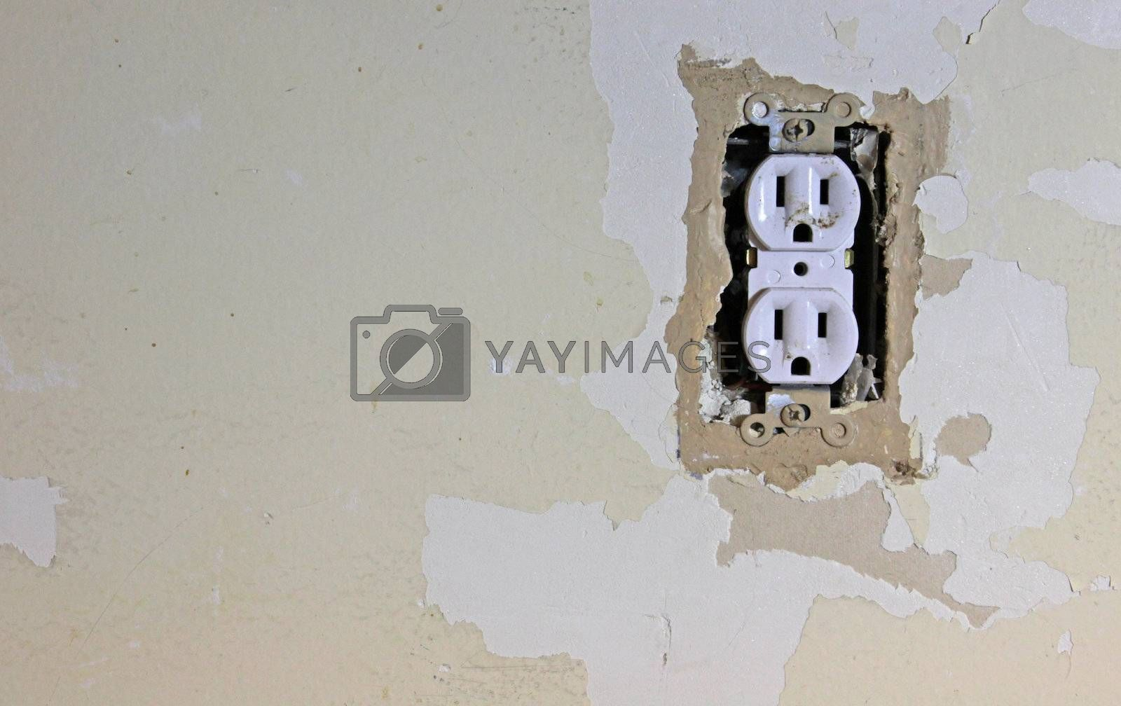 A dirty electrical outlet exposed during a renovation and the surrounding dry wall.