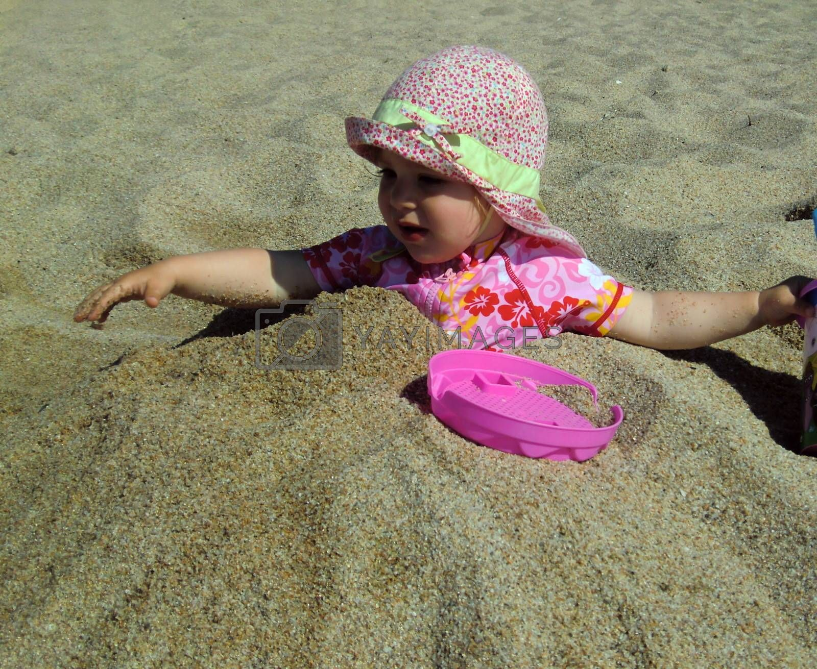 Portrait of little cute blond girl (one year and seven months of age) buried in the sand