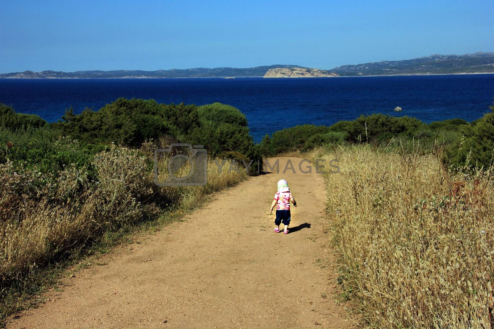Little girl (one year and seven months of age) makes first steps on the  Sardinia ground