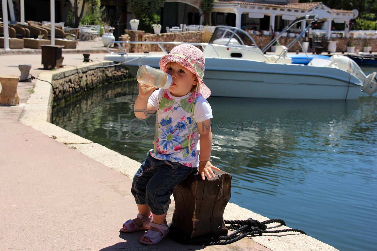 Portrait of little cute blond girl (one year and seven months of age) on the port