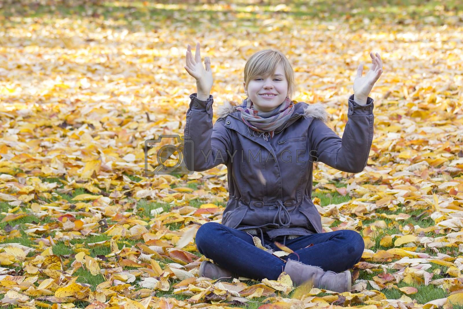 smiling girl sitting on fallen leaves in autumn park and rising up hands