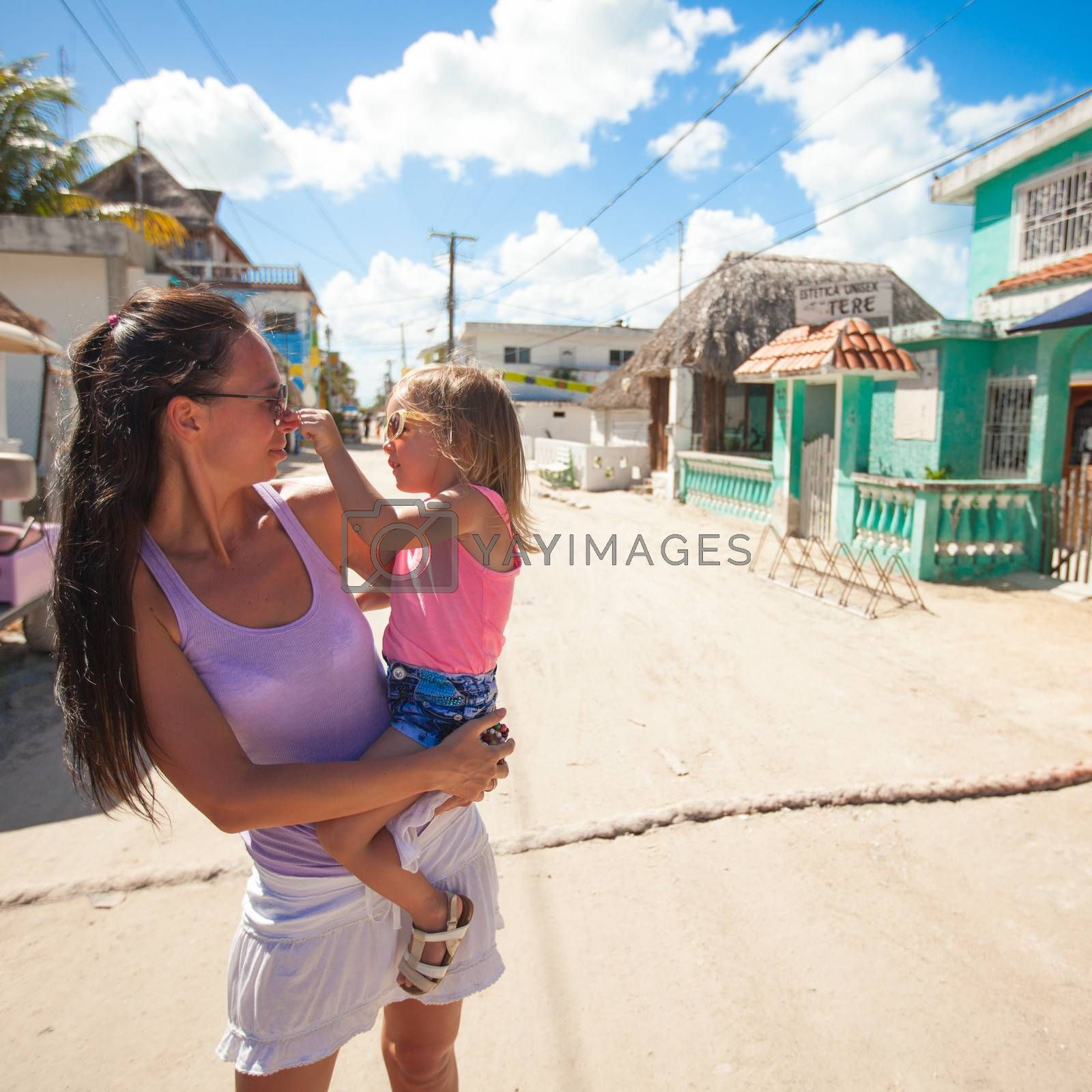 Young mother with her little girl walking on sandy street in exotic country