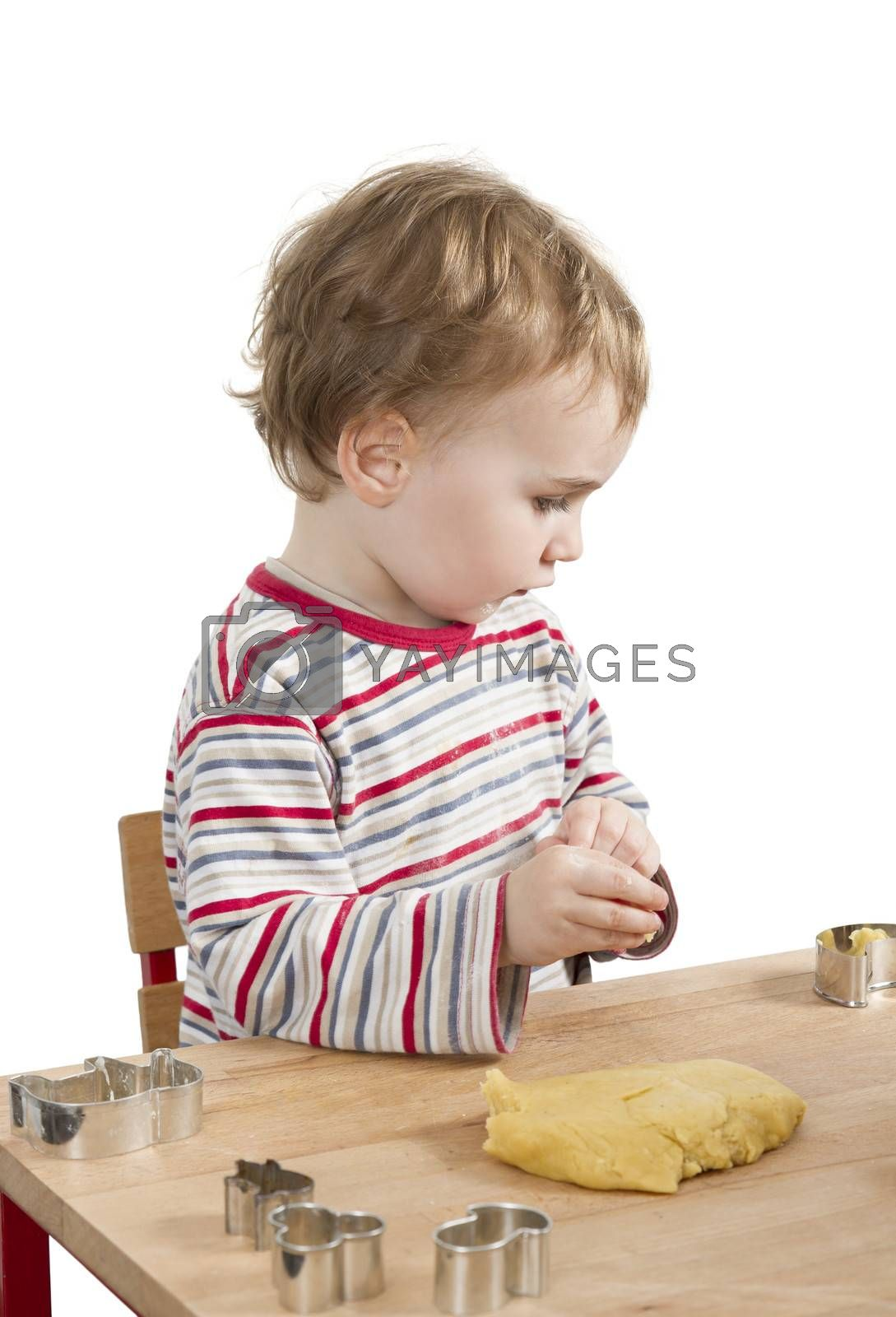young child with dough sitting on desk. vertical image isolated on white background
