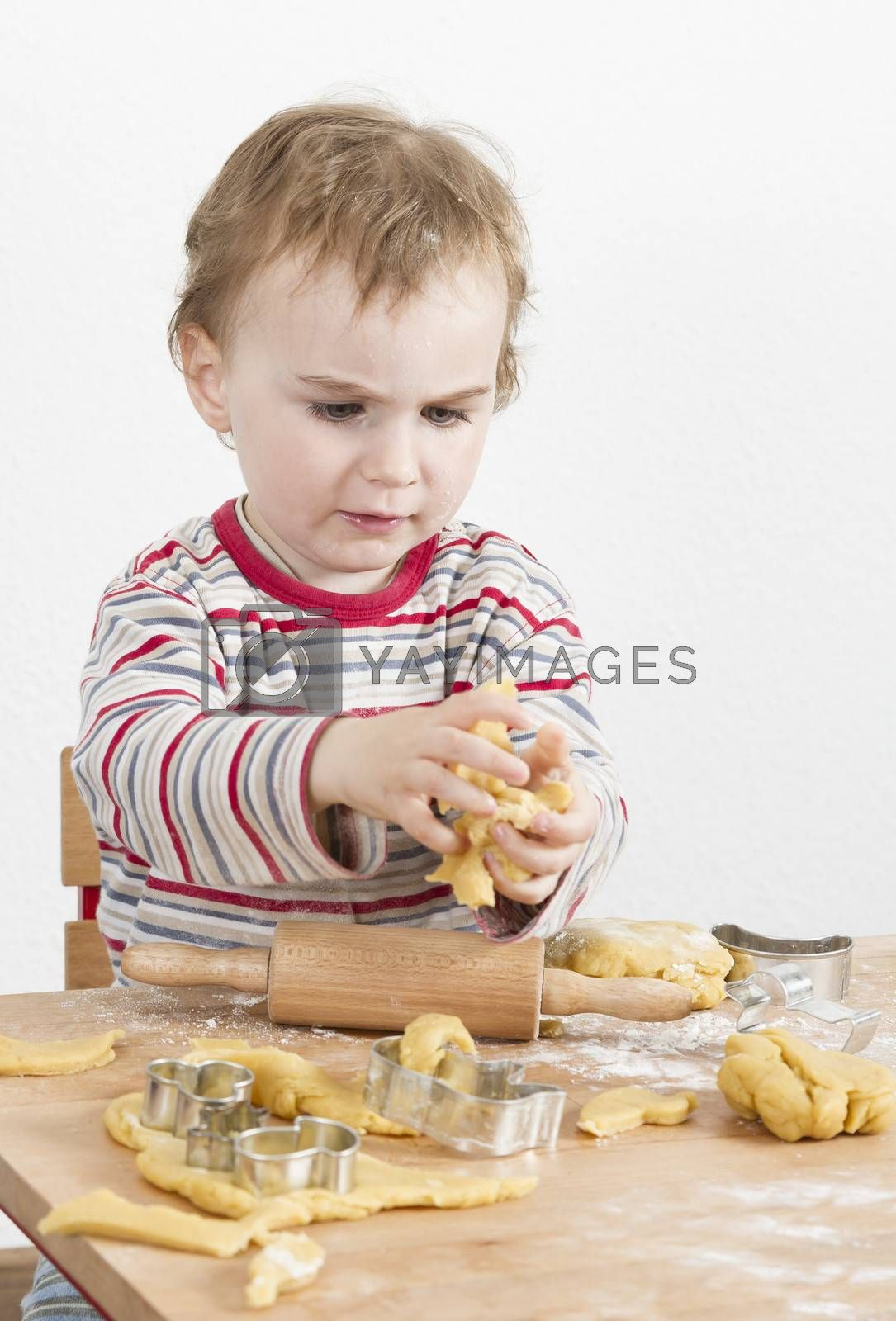 young child in vertical image looking at baking tools and working with dough