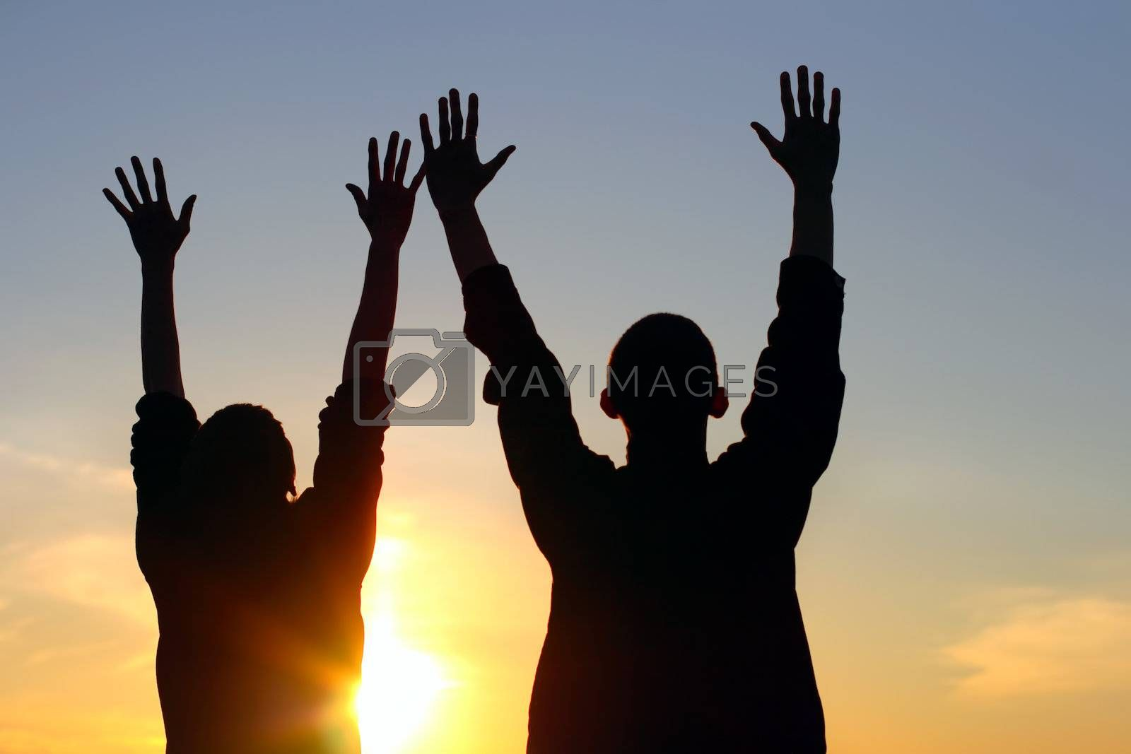 young couple hands up silhouette